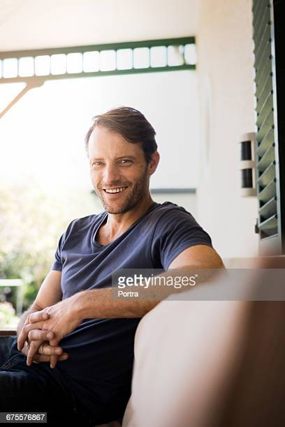 Portrait of mid adult man resting on sofa at porch