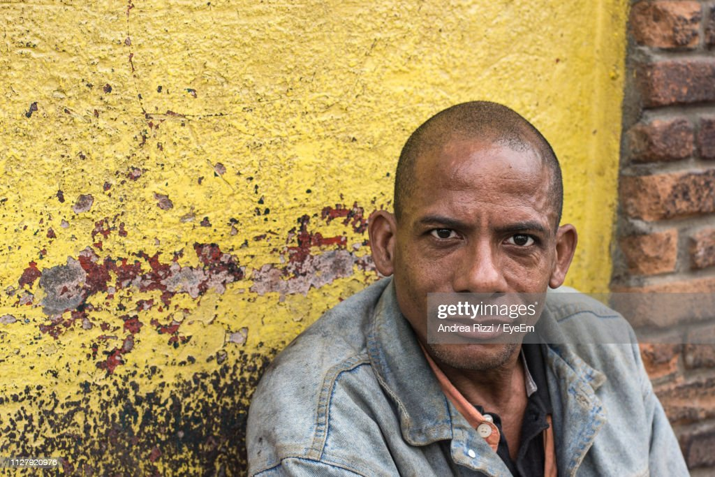 Portrait Of Mid Adult Man Sitting Against Wall : Foto stock