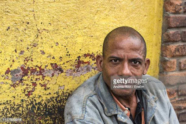 portrait of mid adult man sitting against wall - andrea rizzi stock pictures, royalty-free photos & images