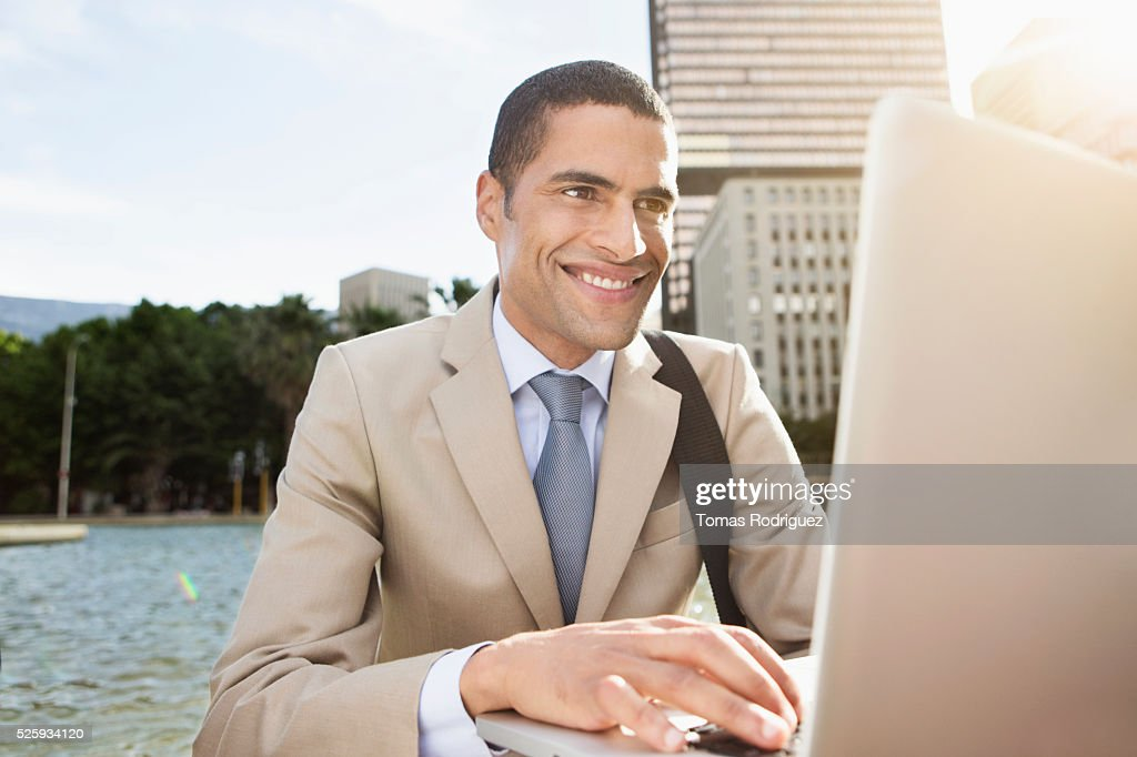 Portrait of mid adult man sitting by fountain and using laptop : Foto de stock