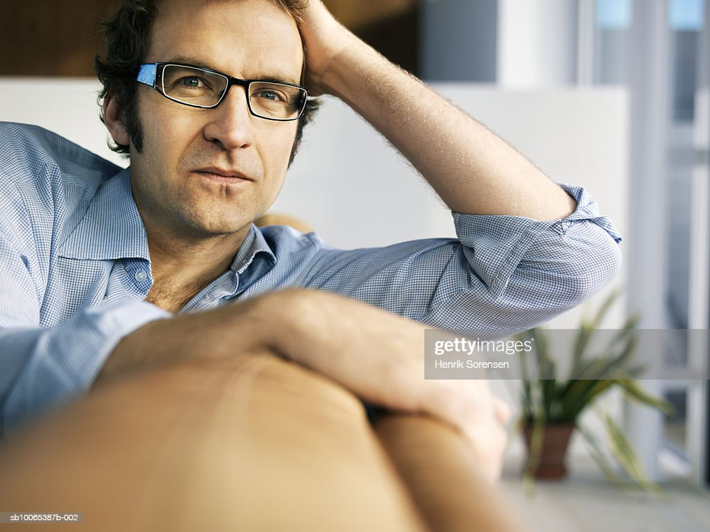 Portrait of mid adult man sitting on sofa, differential focus : Foto stock