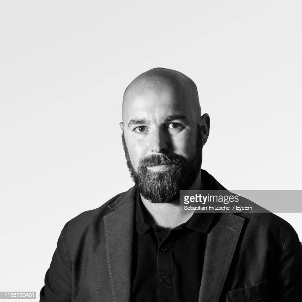 portrait of mid adult man standing against white background - black and white stock pictures, royalty-free photos & images
