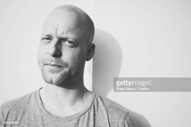 portrait of mid adult man standing against white wall - hair loss stock pictures, royalty-free photos & images