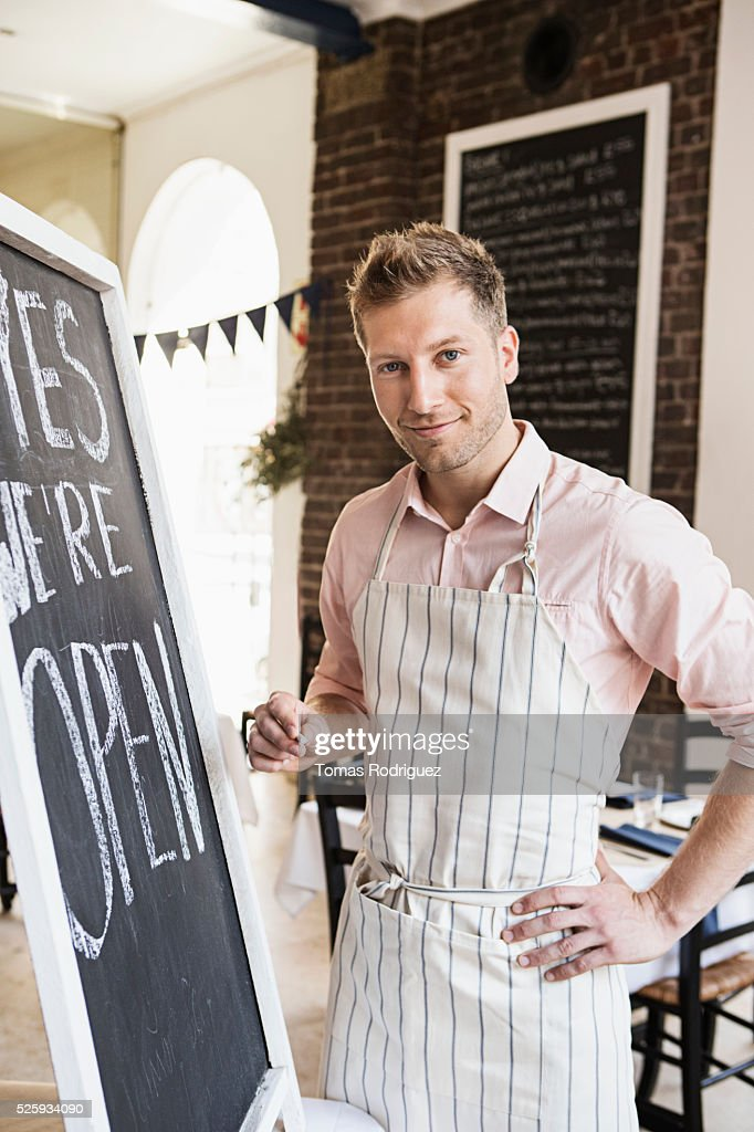 Portrait of mid adult man standing by blackboard open sign : Stock-Foto