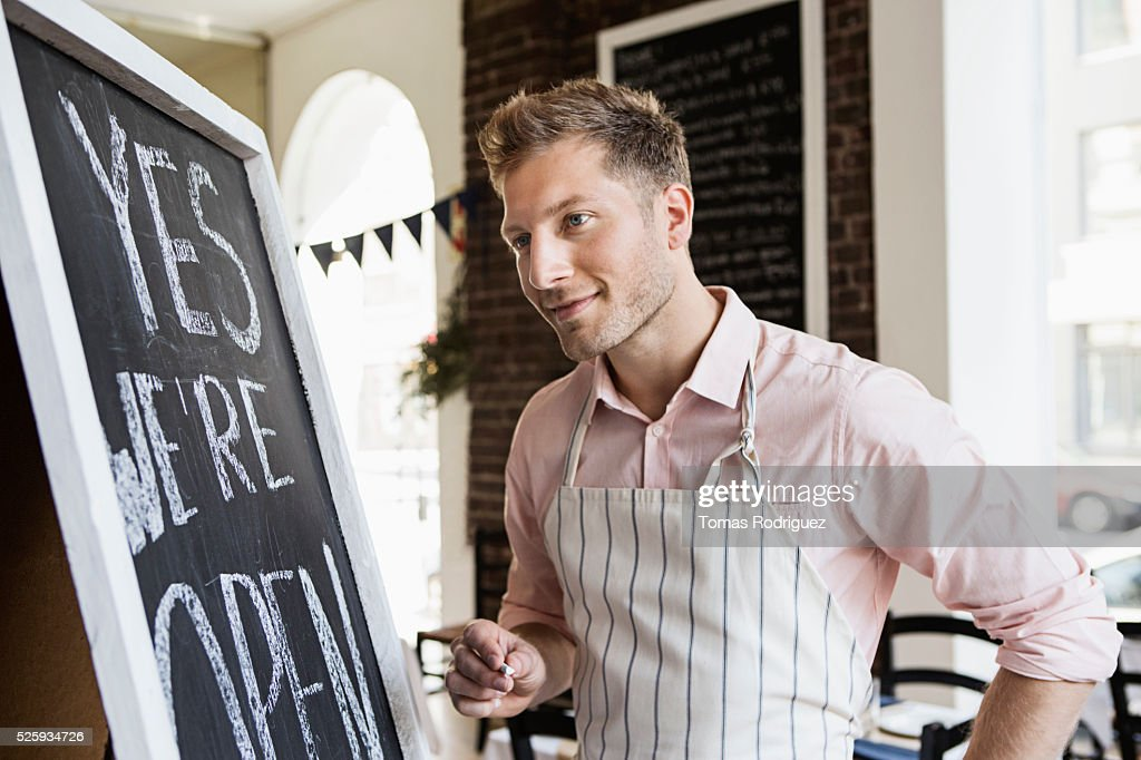 Portrait of mid adult man standing by blackboard open sign : Stock Photo