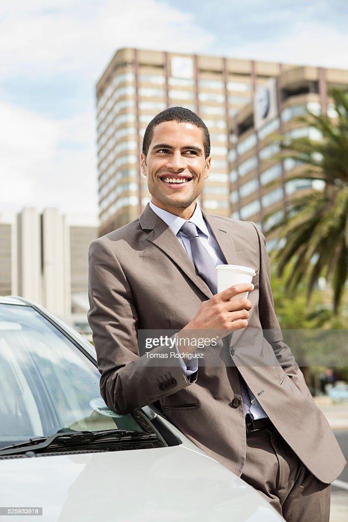 Portrait of mid adult man standing by car with coffee cup : Foto de stock