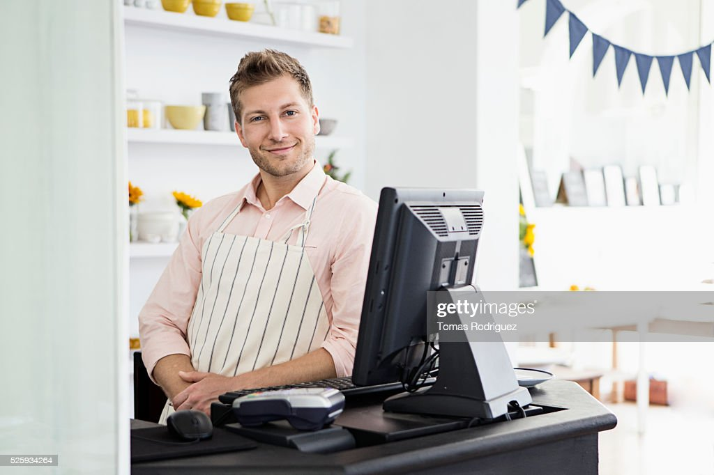 Portrait of mid adult man standing by checkout counter : Stockfoto