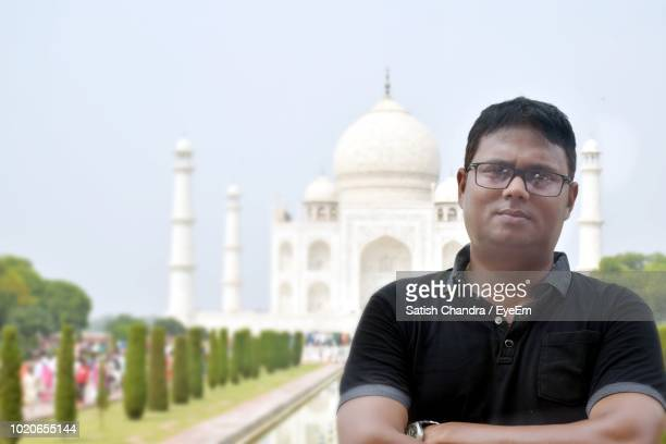 portrait of mid adult man standing with arms crossed against taj mahal - mid adult men stock pictures, royalty-free photos & images