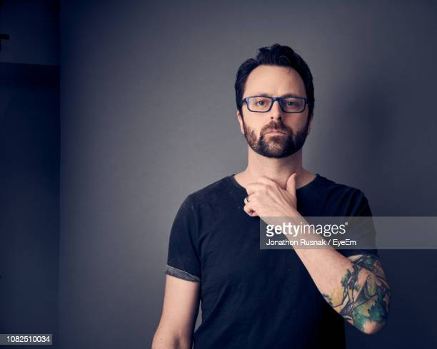 portrait of mid adult man swearing against wall - oath stock pictures, royalty-free photos & images