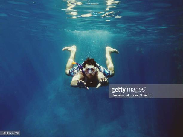 portrait of mid adult man swimming in sea - underwater diving stock pictures, royalty-free photos & images