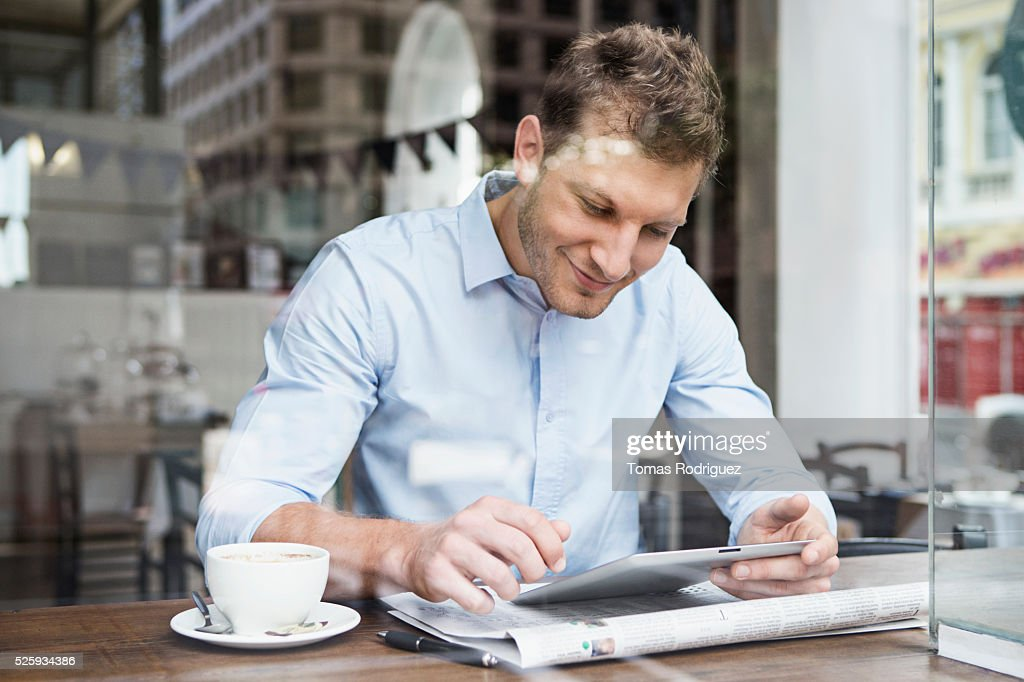 Portrait of mid adult man using digital tablet at cafe : Stock-Foto