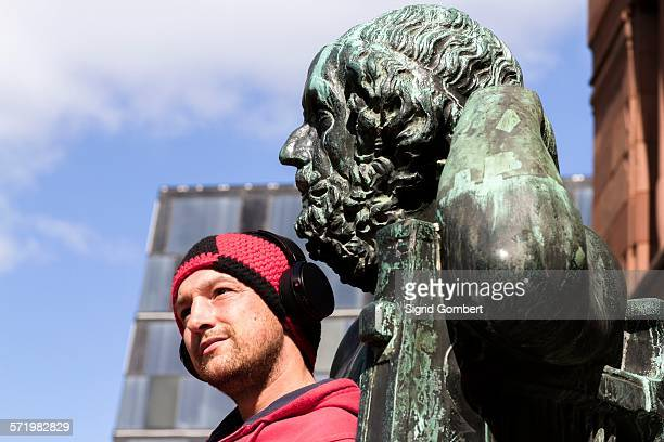 portrait of mid adult man wearing headphones in front of sculpture, freiburg, baden, germany - sigrid gombert stock pictures, royalty-free photos & images