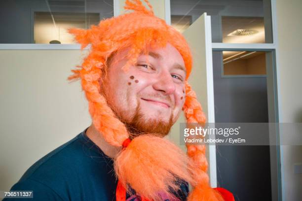 portrait of mid adult man wearing orange wig at home - goatee stock pictures, royalty-free photos & images