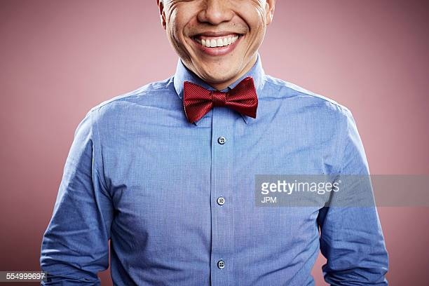 portrait of mid adult man wearing red tie, smiling - bow tie stock pictures, royalty-free photos & images