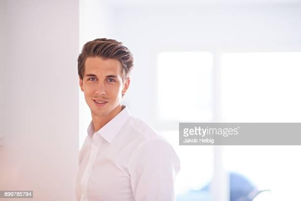 portrait of mid adult man wearing white shirt in living room - 白いシャツ ストックフォトと画像
