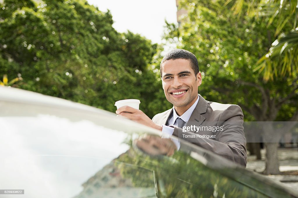 Portrait of mid adult man with coffee cup leaning on car : Photo