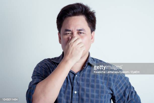 portrait of mid adult man with hand covering nose while standing against white background - olor desagradable fotografías e imágenes de stock