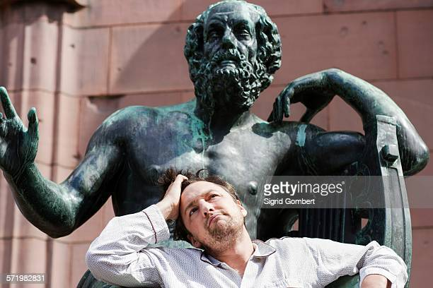 portrait of mid adult man with hand in hair in front of sculpture, freiburg, baden, germany - sigrid gombert stock pictures, royalty-free photos & images