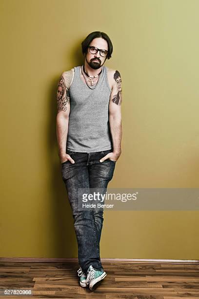 Portrait of mid adult man with tattoos, studio shot