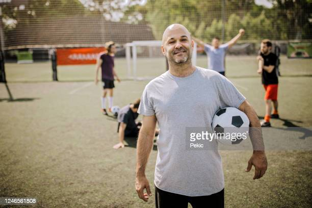 portrait of mid adult men on soccer field - amateur stock pictures, royalty-free photos & images