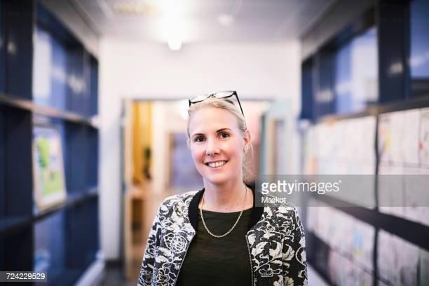 portrait of mid adult teacher smiling in school corridor - 校長 ストックフォトと画像