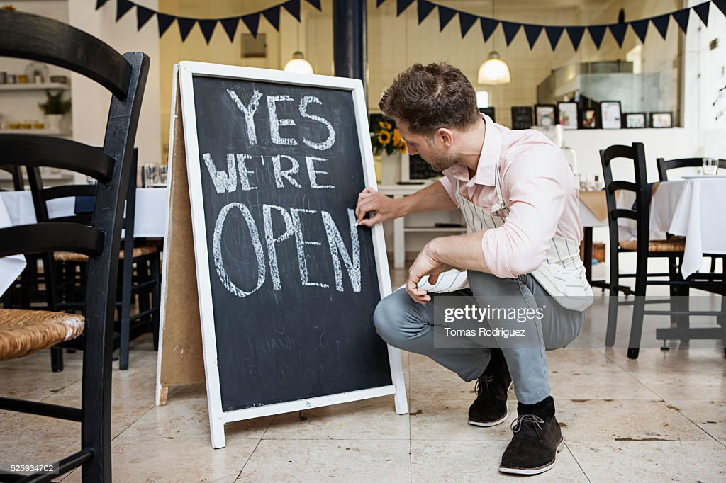 Portrait of mid adult waiter crouching by blackboard and writing : Stock Photo