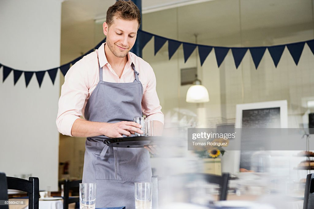 Portrait of mid adult waiter holding tray : Stock Photo
