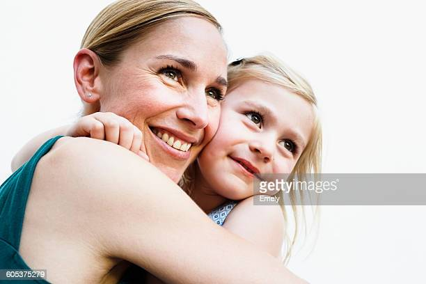 Portrait of mid adult woman and daughter hugging in front of white wall