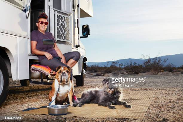portrait of mid adult woman and two dogs sitting on camper van step, borrego springs, california, usa - nomadic people stock pictures, royalty-free photos & images