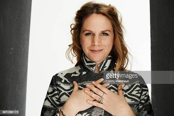 portrait of mid adult woman crossed hands on chest - geschworener stock-fotos und bilder