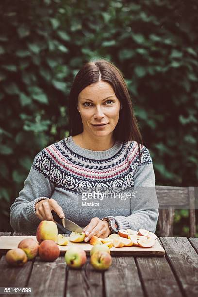Portrait of mid adult woman cutting apples at table in organic farm