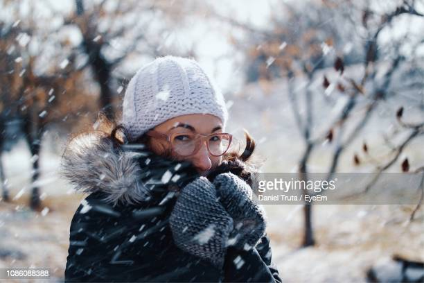 portrait of mid adult woman during snowfall - knit hat stock pictures, royalty-free photos & images