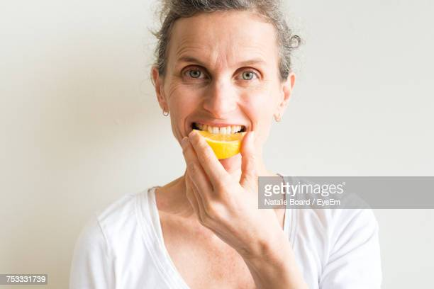 Portrait Of Mid Adult Woman Eating Orange While Standing Against White Background