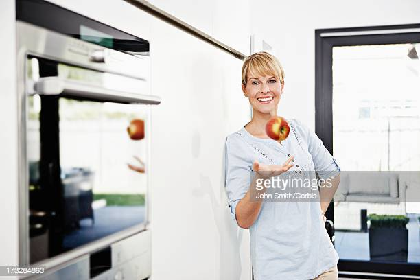 portrait of mid adult woman holding apple - donne di età media foto e immagini stock
