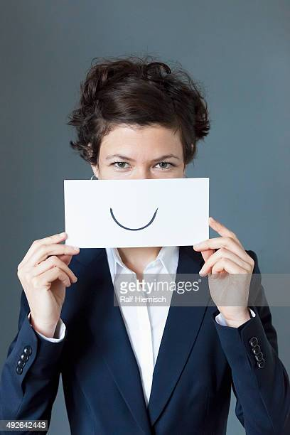 portrait of mid adult woman holding paper with curve sign, close-up - smiley face stock pictures, royalty-free photos & images