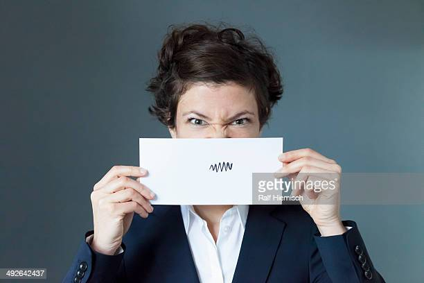 Portrait of mid adult woman holding paper with zigzag sign, close-up