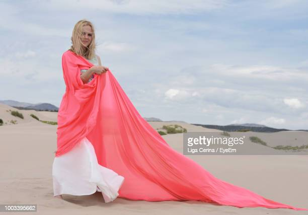 portrait of mid adult woman holding pink scarf on sandy beach - liga cerina stock pictures, royalty-free photos & images