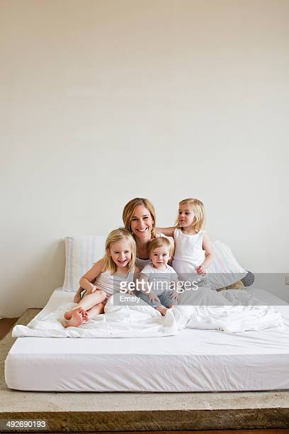 Portrait of mid adult woman in bed with three daughters