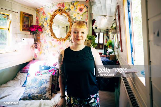 portrait of mid adult woman in cozy bedroom on narrowboat - ambient light stock pictures, royalty-free photos & images