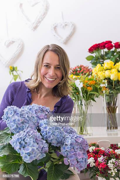portrait of mid adult woman in flower shop, smiling - mid adult women stock pictures, royalty-free photos & images