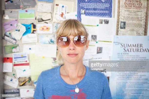 portrait of mid adult woman in front of community notice board - heshphoto foto e immagini stock