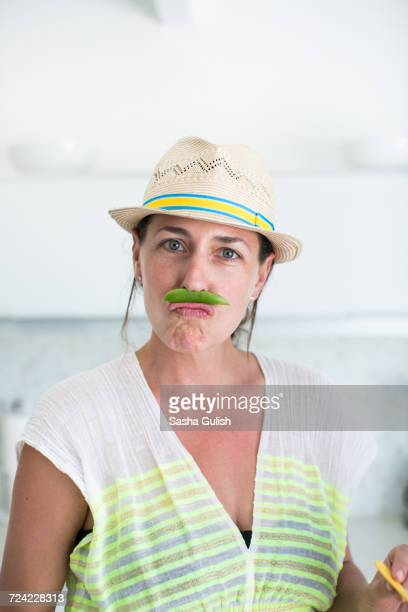 Portrait of mid adult woman in straw hat and pea pod moustache