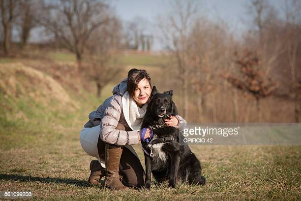 Portrait of mid adult woman kneeling with her dog in field