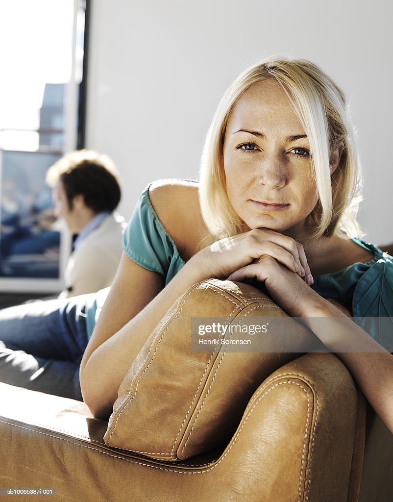 Portrait of mid adult woman leaning on sofa, man in background : Foto stock