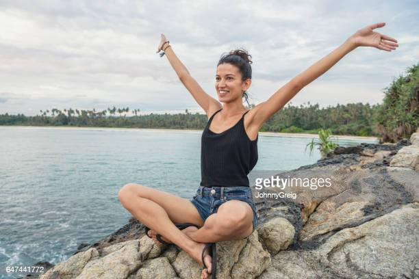Portrait of mid adult woman on rocks with arms out, smiling