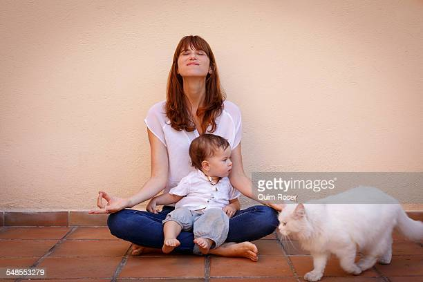 Portrait of mid adult woman practicing yoga with baby daughter on kitchen floor