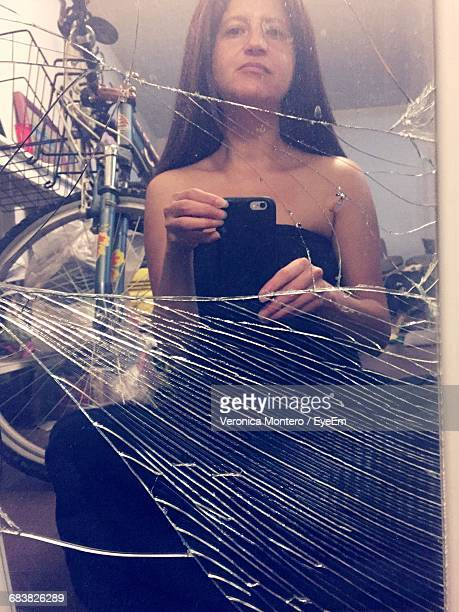 Portrait Of Mid Adult Woman Reflecting On Shattered Glass While Taking Selfie