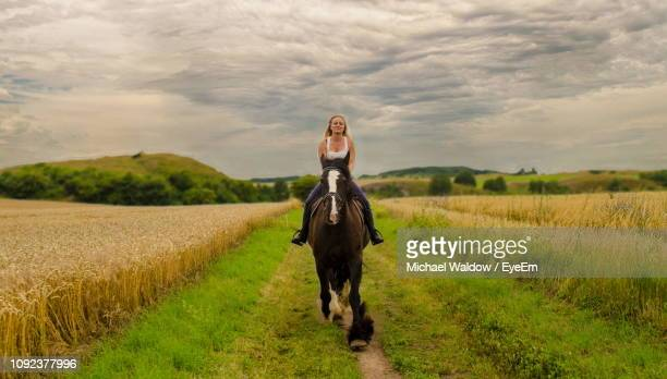 portrait of mid adult woman riding horse on grassy field against cloudy sky - saxony anhalt stock pictures, royalty-free photos & images
