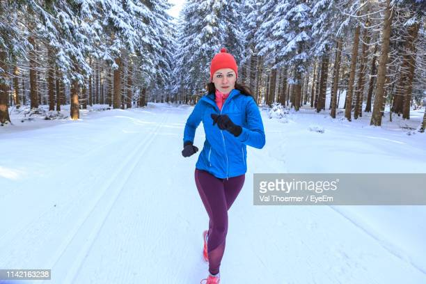 portrait of mid adult woman running on snow covered field against trees in forest - val thoermer stock-fotos und bilder