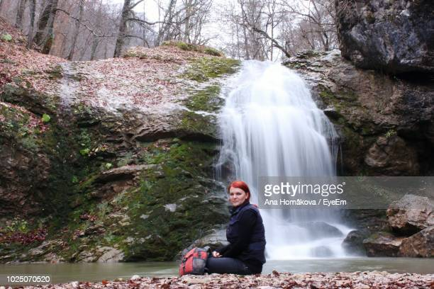 Portrait Of Mid Adult Woman Sitting Against Waterfall In Forest